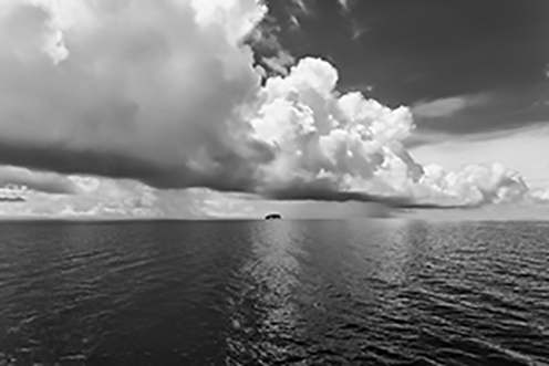 black and white photo of clouds and sea