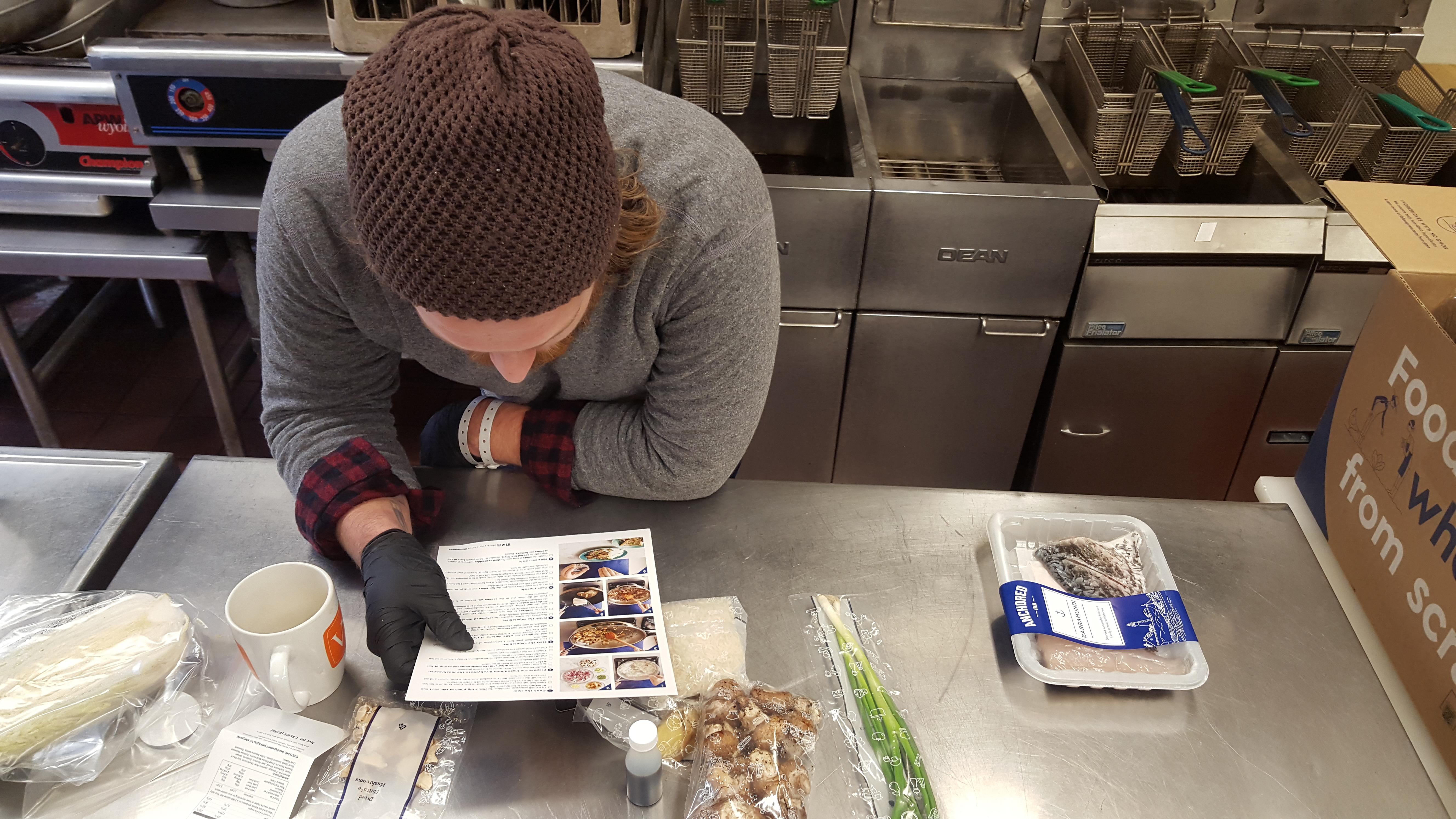 Chef Max Miller Reading the Blue Apron Barramundi Recipe