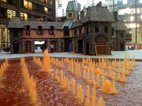 Photo of Chicago's Daley Center decorated for Halloween with a haunted house and fountains that have been dyed orange
