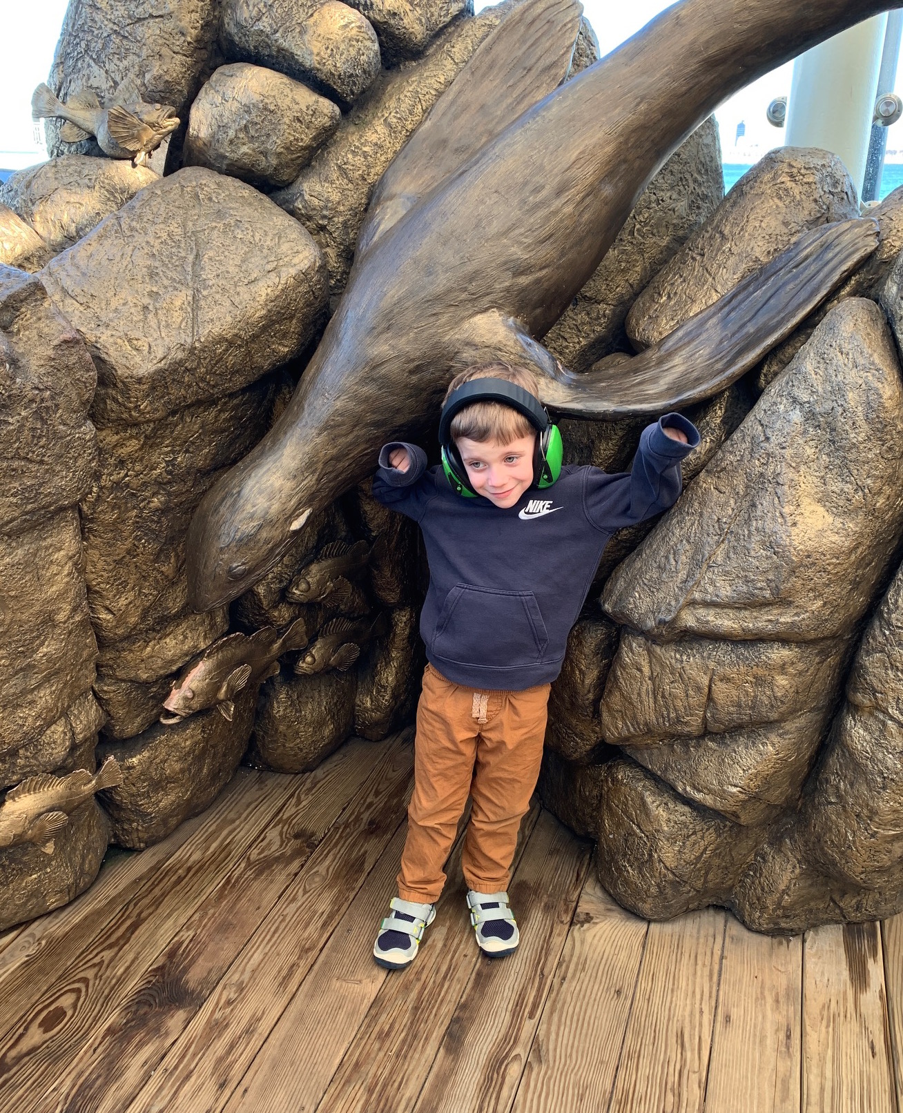A boy wearing noise-cancelling headphones stands in front of a statue of a seal and fish