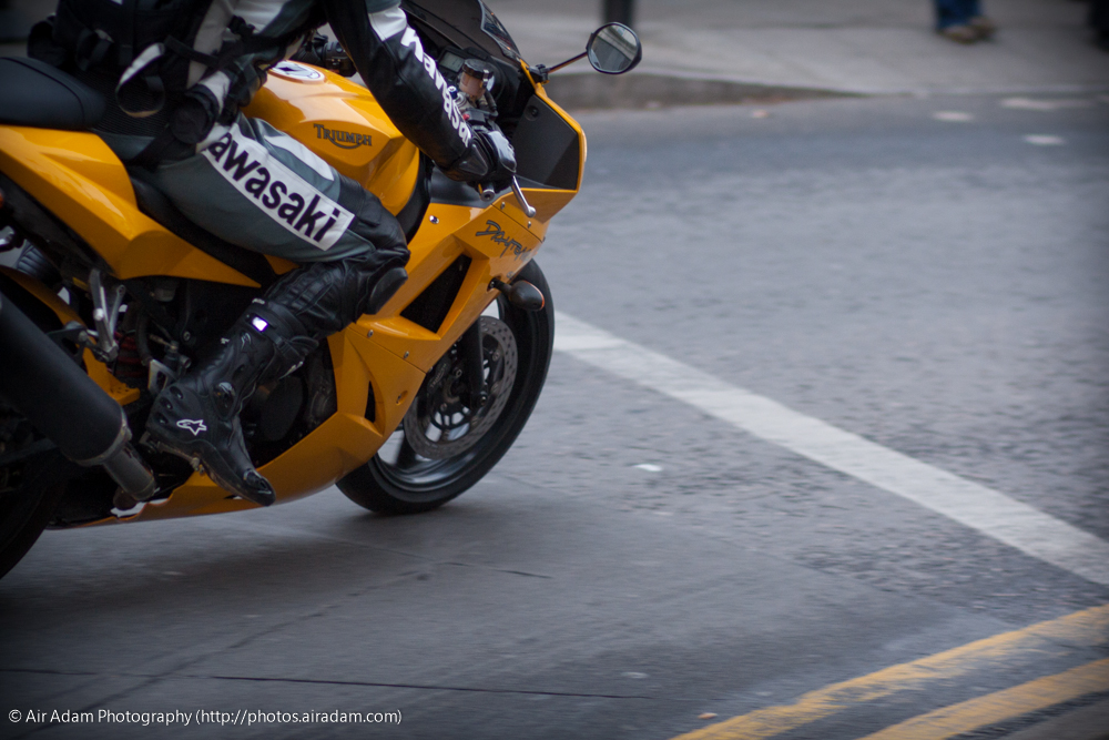 Yellow motorbike rounding corner, with double yellow lines
