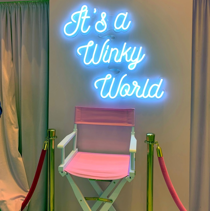 "Winky Lux neon sign says ""It's a Winky world."""