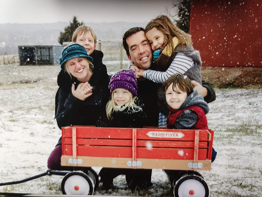 family huddled in snow, smiling