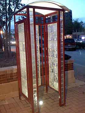 Photo of Cell Phone Booth, a piece of public art by sculptor Ed Francis on display at the train station in Arlington Heights, Illinois