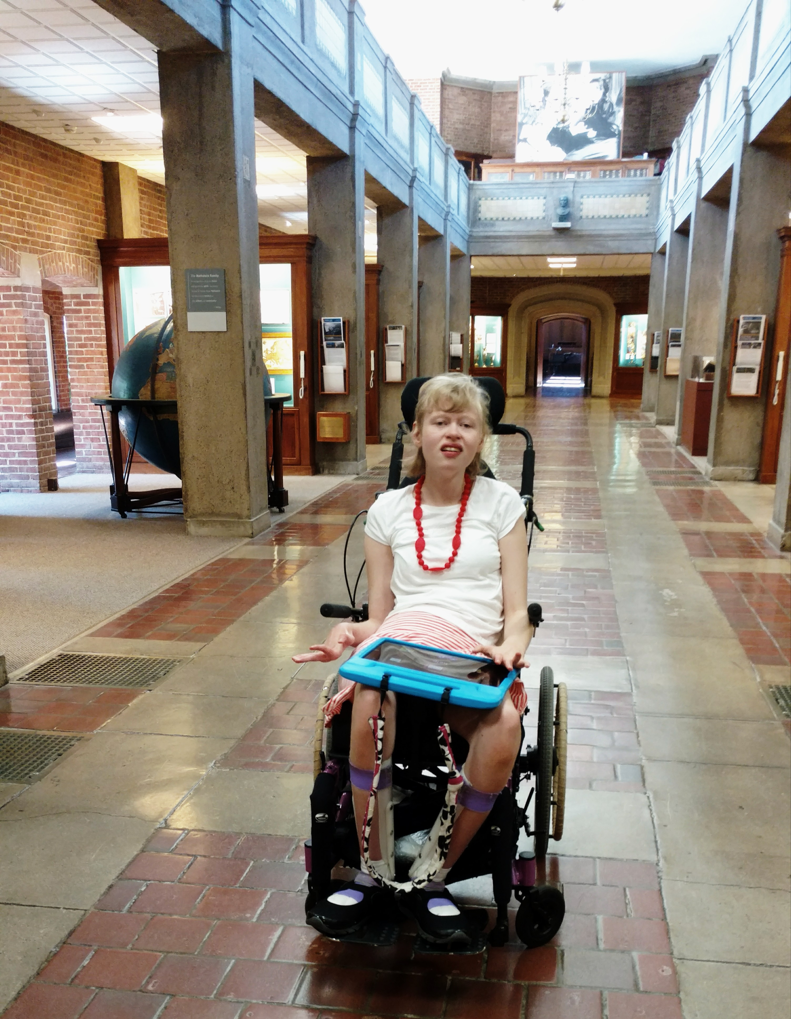 Emma sits in wheelchair with tablet on lap in corridor