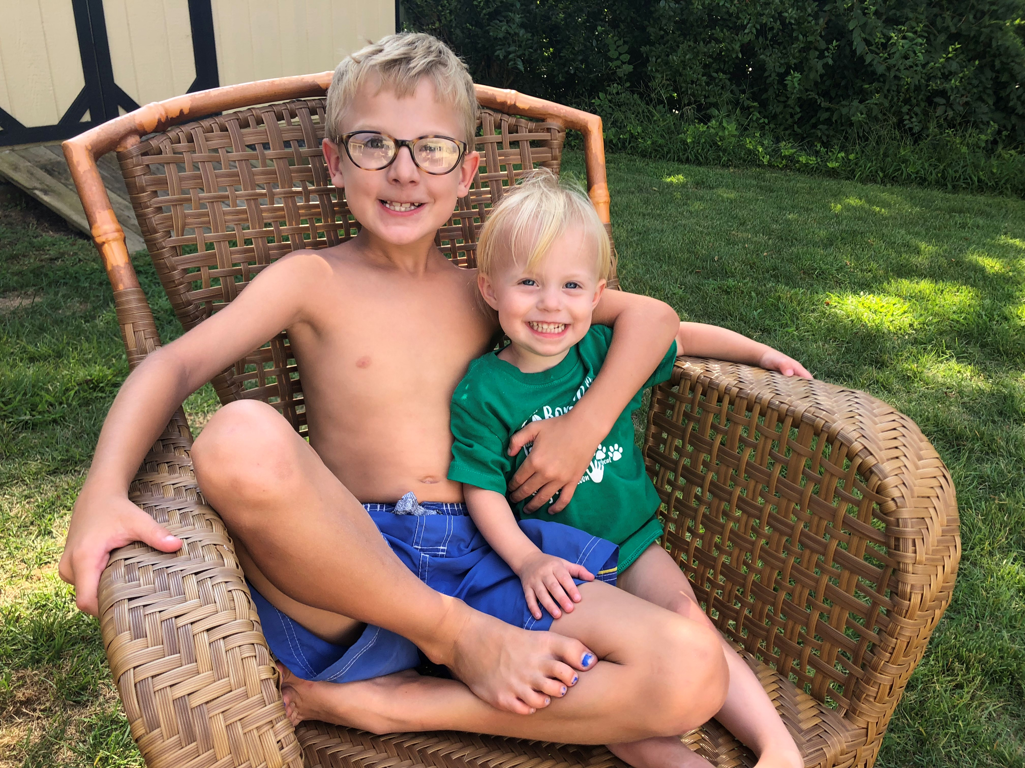 Big brother and little sister side-by-side in wicker chair