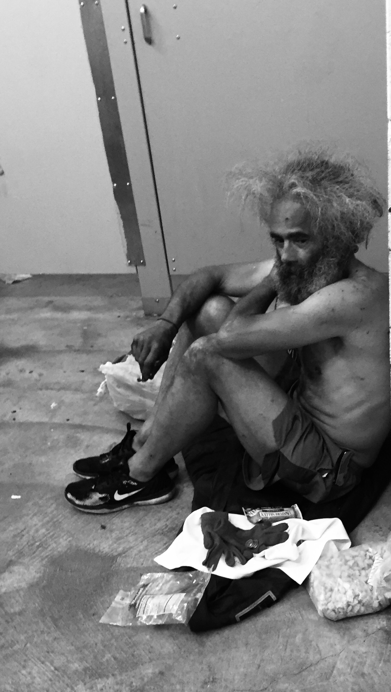 black and white photograph of a drug addict squatting on the floor of a bathroom