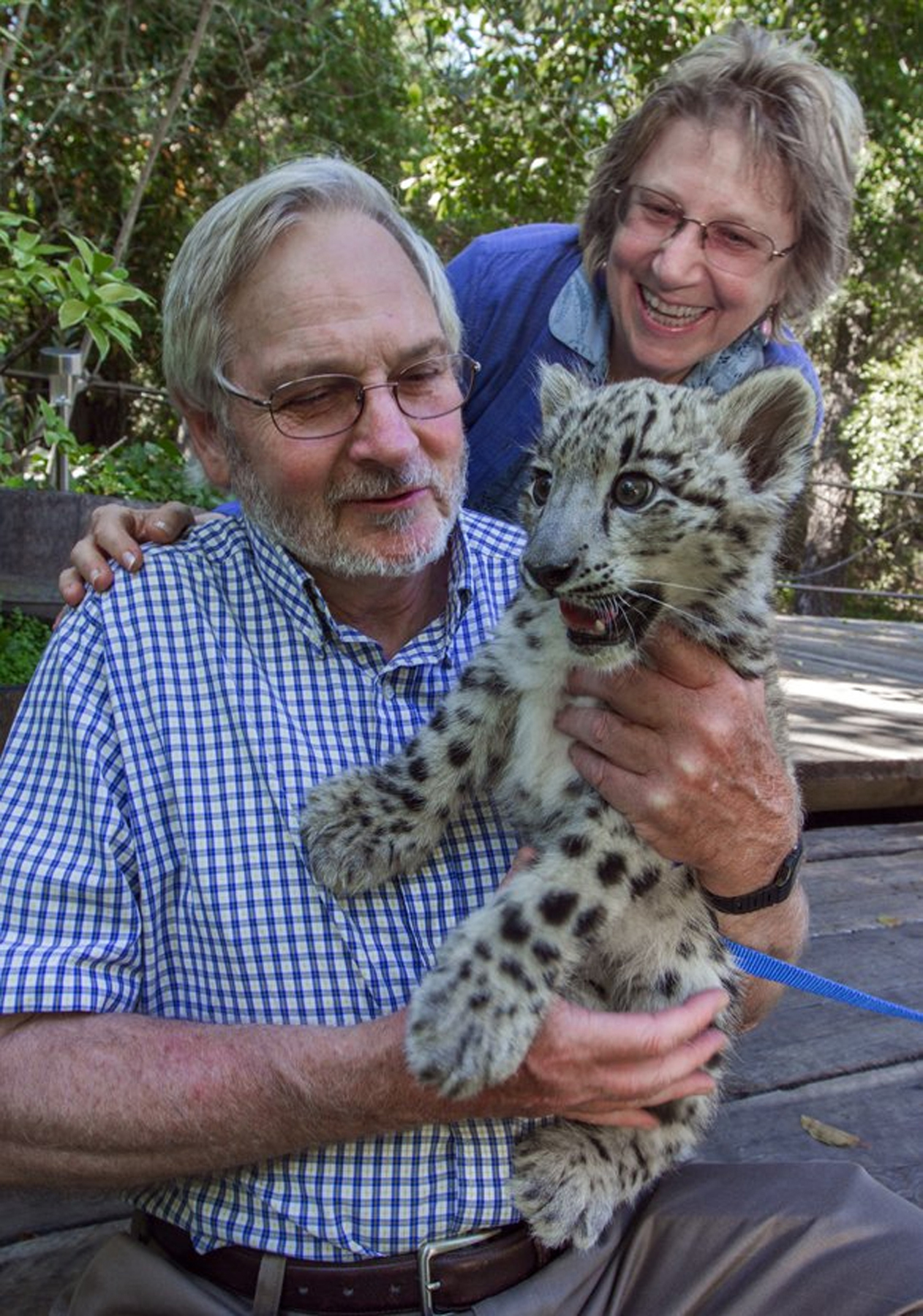 Rodney Jackson and Darla Hillard with snow leopard cub, Jackson. Photo credit: Robbi Pengally