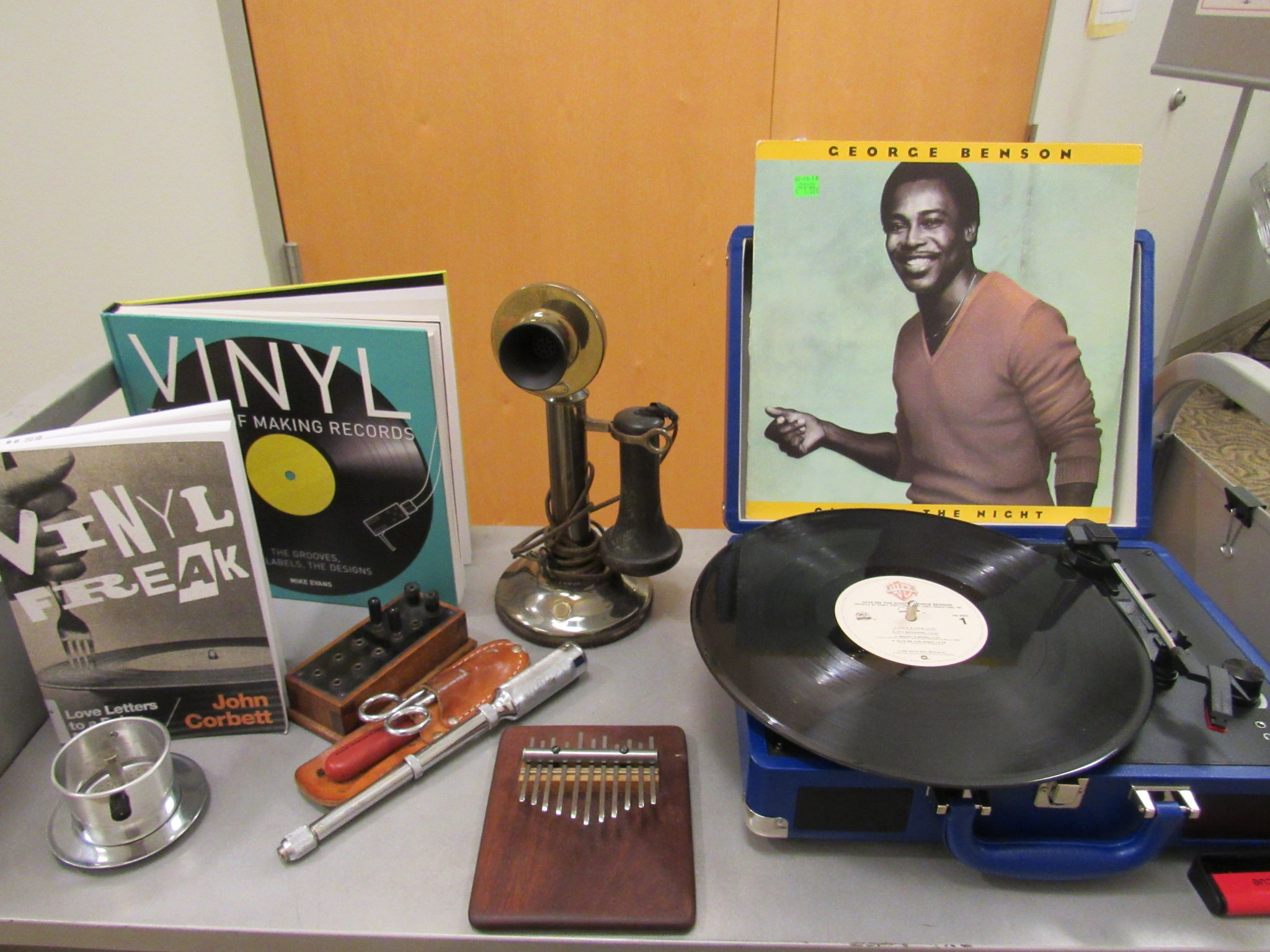 Retro tech collection including a vinyl record and player, an old fashioned phone, and a thumb piano.